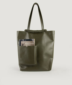 Pazar Book Tote bag from Italian calf leather in olive green. Hand braided signature leather handle functioning as a fastening detail. The outside pocket is designed for a book. This size is suitable for A4 format, all MacBook and iPad sizes.