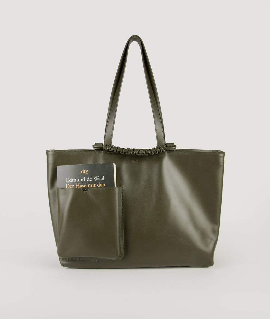 Pazar Tote bag from Italian calf leather in olive green, wide size. Hand braided signature leather handle functioning as a fastening detail. The outside pocket is designed for a book. This size is suitable for A4 format, all MacBook and iPad sizes.