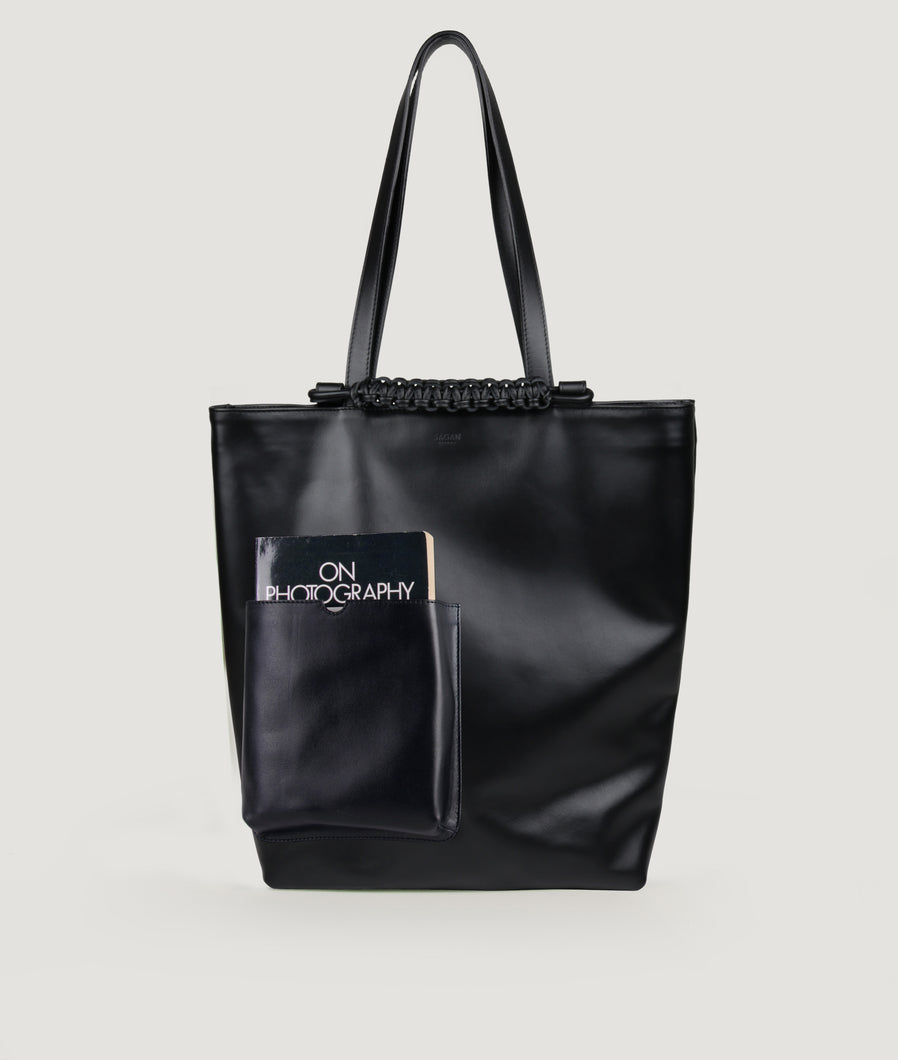 Pazar Book Tote bag from Italian calf leather in black. Hand braided signature leather handle functioning as a fastening detail. The outside pocket is designed for a book. This size is suitable for A4 format, all MacBook and iPad sizes.