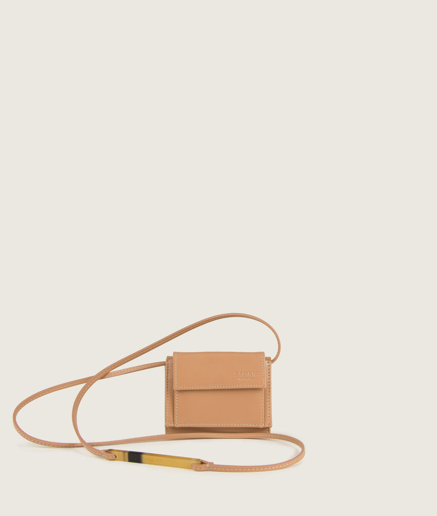 The Triptych mini wallet bag in nude is made from Italian smooth calf leather. The strap comes with a horn element. This compact format is perfect to fit cards, as well as bills and coins. Familiar done differently.