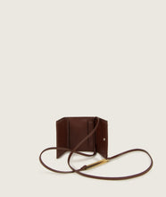 Load image into Gallery viewer, the Triptych mini wallet bag in brown is made from Italian smooth calf leather. The strap comes with a horn element. This compact format is perfect to fit cards, as well as bills and coins. Familiar done differently.