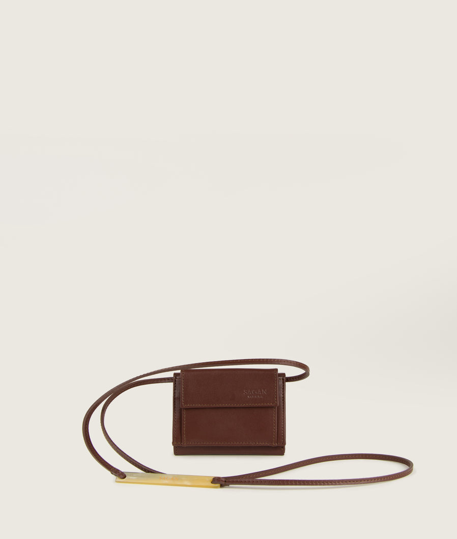 the Triptych mini wallet bag in brown is made from Italian smooth calf leather. The strap comes with a horn element. This compact format is perfect to fit cards, as well as bills and coins. Familiar done differently.