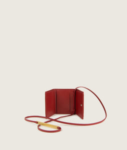 The Triptych mini wallet bag in red is made from Italian smooth calf leather. The strap comes with a horn element. This compact format is perfect to fit cards, as well as bills and coins. Familiar done differently.