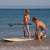 SUP lesson. Dad wears SBB Mens Retro Trunks in Tribal, Son wears SBB Kids Going Out Boardies in Hooray for Fish!