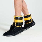 Black and yellow ankle weights on male model with black trainers