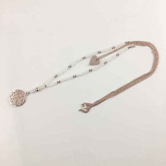 Rose gold white beaded necklace with filigree pendant and smaller heart pendant on chain