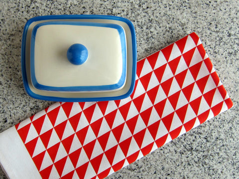 Geometric style, red triangles tea towel with blue and white butter dish on marble countertop [thedasherie.com]