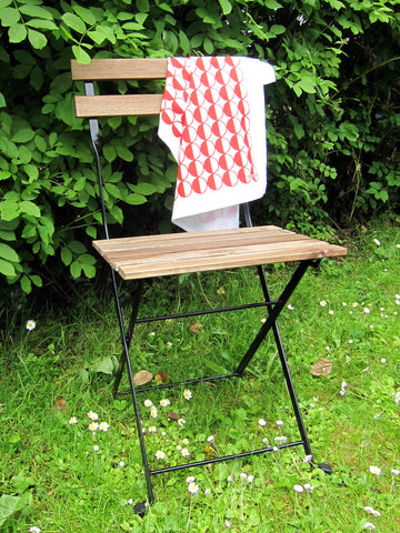 Red Half Circles tea towel draped on bistro chair in front of leafy hedge [thedasherie.com]