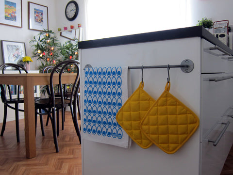 Scandinavian style blue deviled eggs tea towel hanging on end of peninsula unit with yellow oven mitts [thedasherie.com]