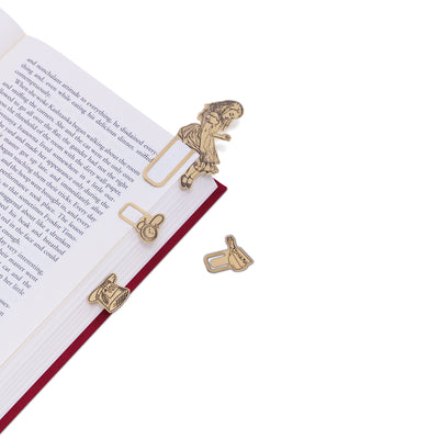 image of Alice in Wonderland Brass Bookminders clipped on the side of an open red book