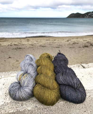Three skeins of yarn on a wall at beach