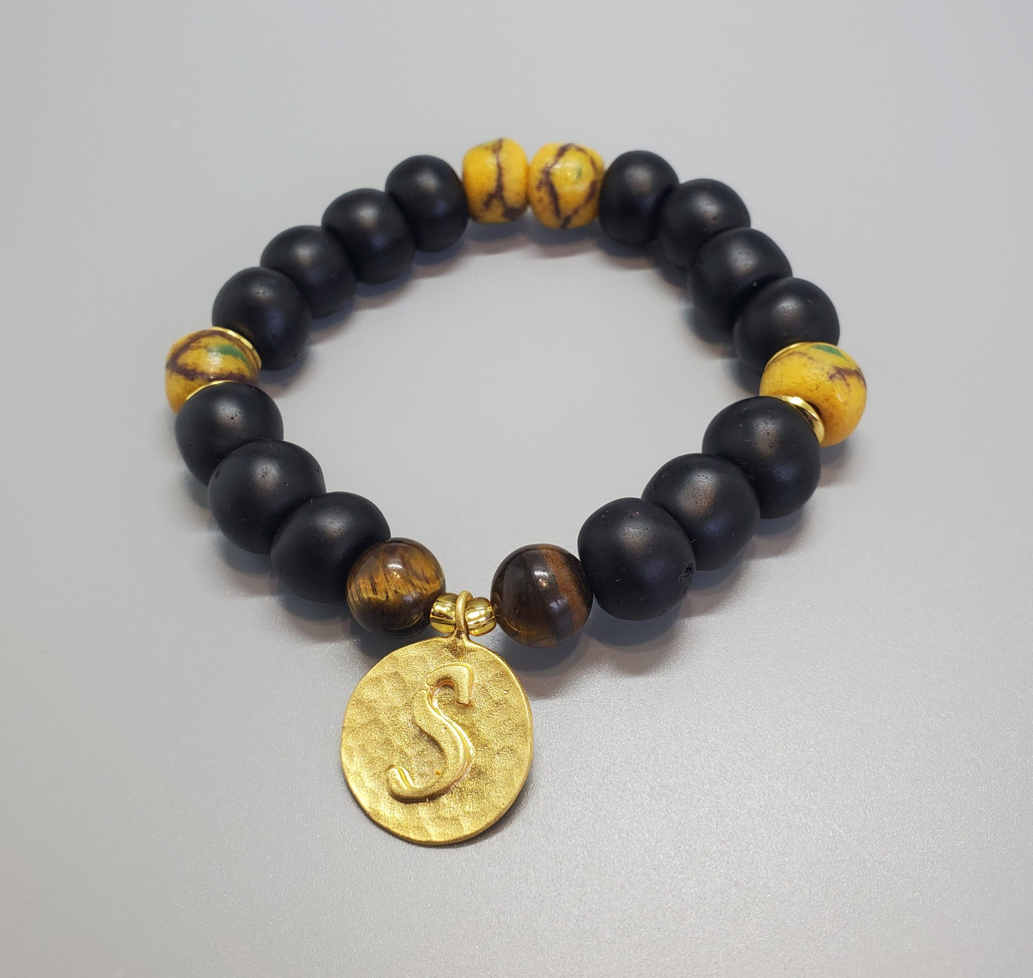 "Black, Must. Krobo Beads, Tiger Eye, 22K Gold Plated Plated Brass ""S"" Charm, Brass, Unisex Stretch Bracelet"