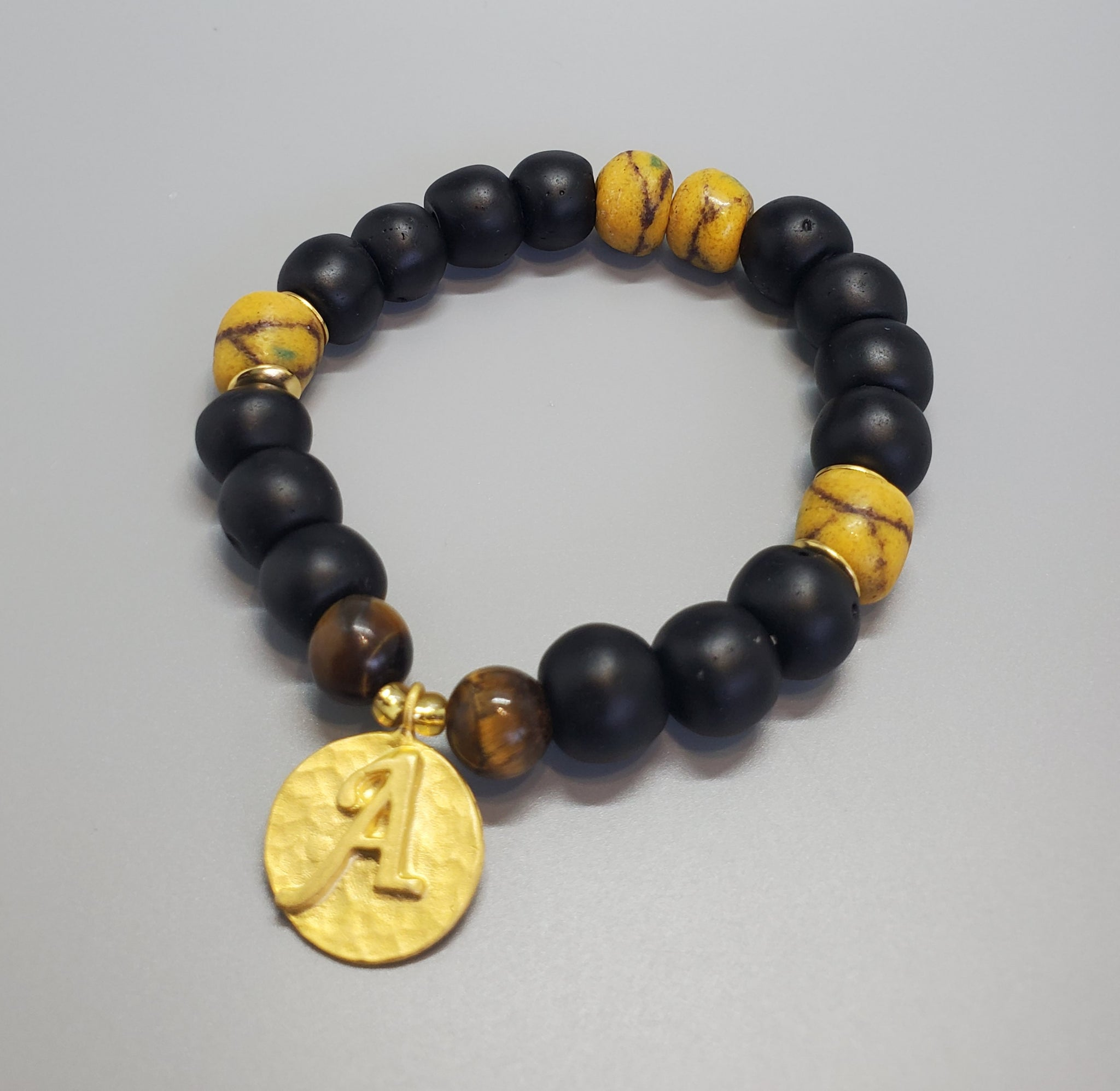 "Black, Must. Krobo Beads, Tiger Eye, 22K Gold Plated Plated Brass ""A"" Charm, Brass, Unisex Stretch Bracelet"
