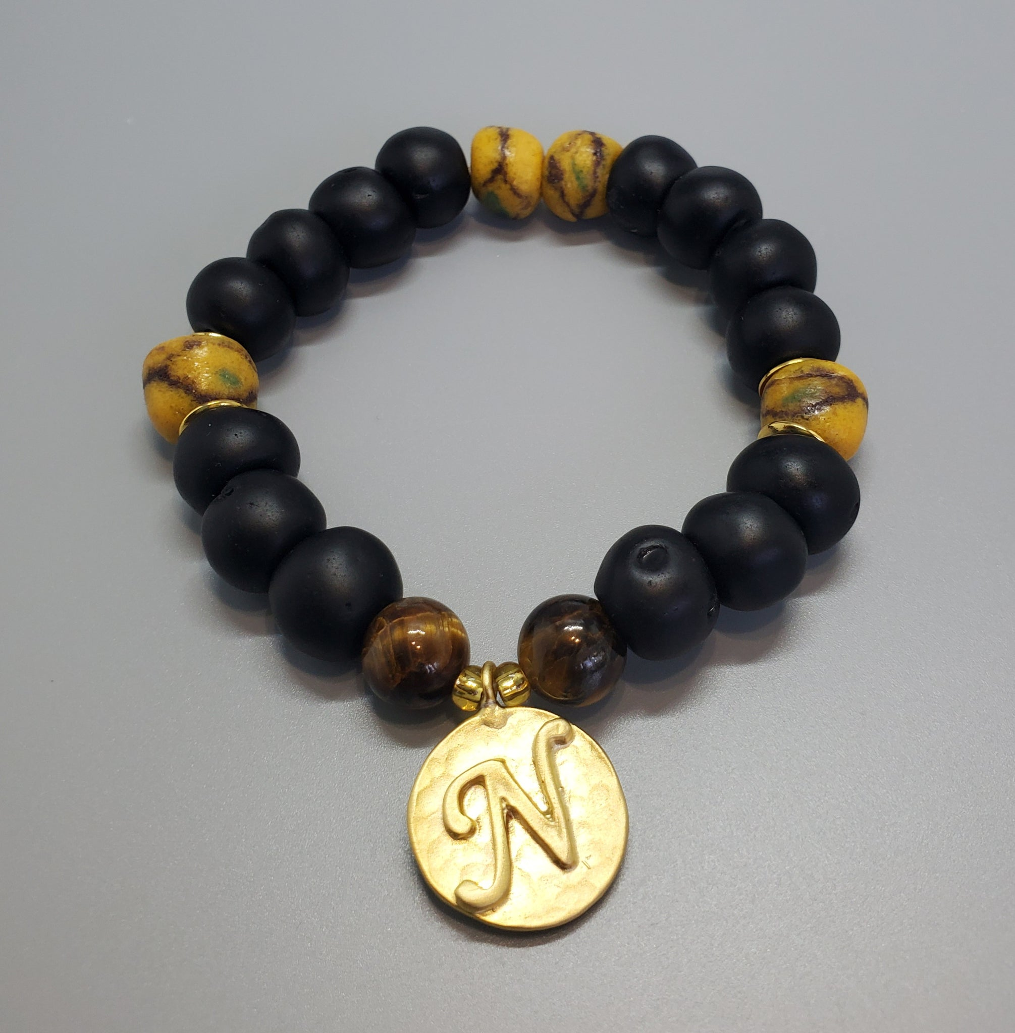 "Black, Must. Krobo Beads, Tiger Eye, 22K Gold Plated Plated Brass ""N"" Charm, Brass, Unisex Stretch Bracelet"
