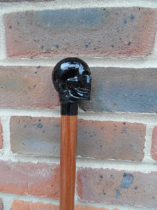 A Brass Skull Handle Walking Stick on a Bubinga, Olive and Zebrano Wood Shank.