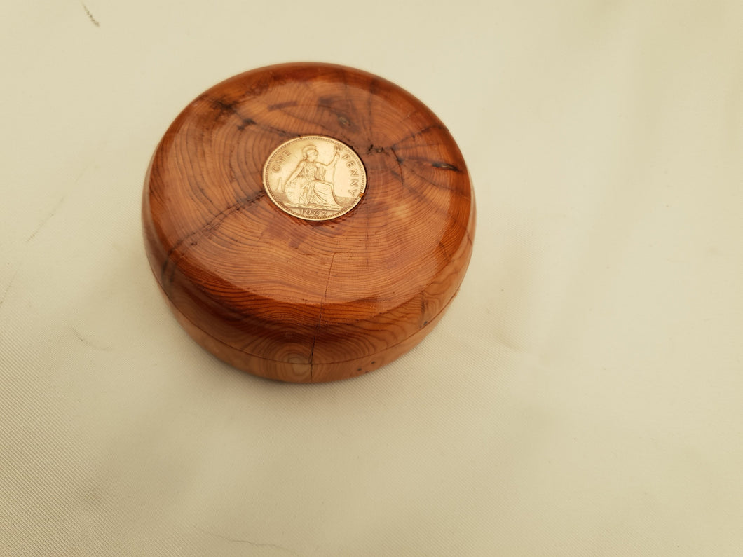A Brass 100 Year Calender Within a Beautifully Hand Turned Yew Round Box. A pre Decimal Penny is secured to the Lid