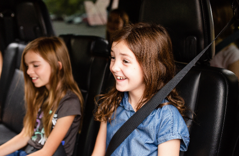 Two young kids play the family conversation starter game on the way to school in the car