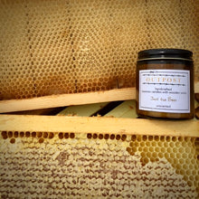 Load image into Gallery viewer, unscented beeswax candle sits on beehive frame