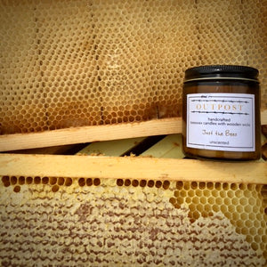 unscented beeswax candle sits on beehive frame
