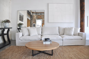 Modular sofa light coloured linen, floor standing mirrors and Natural timber coffee table