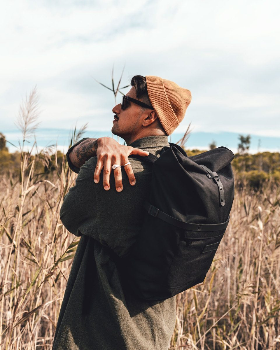 Man with sunglasses and light brown wool hat in a country field wearing the Alldaypack at the back - The miminalistic everyday laptop backpack