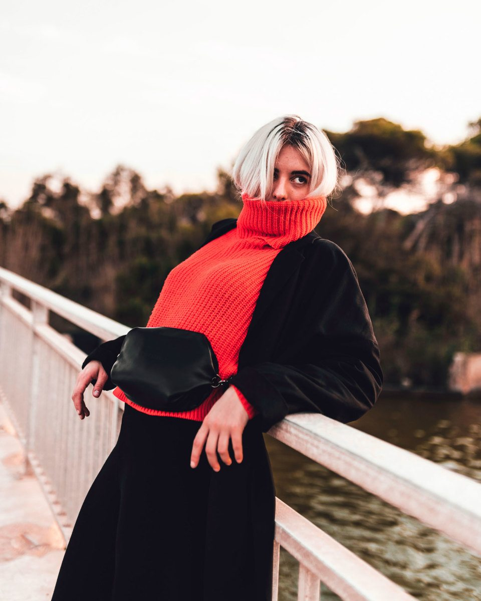 Blond girl standing at a bridge  with a red wool sweater, black jacket and black skirt with the Bumbag black in the waist