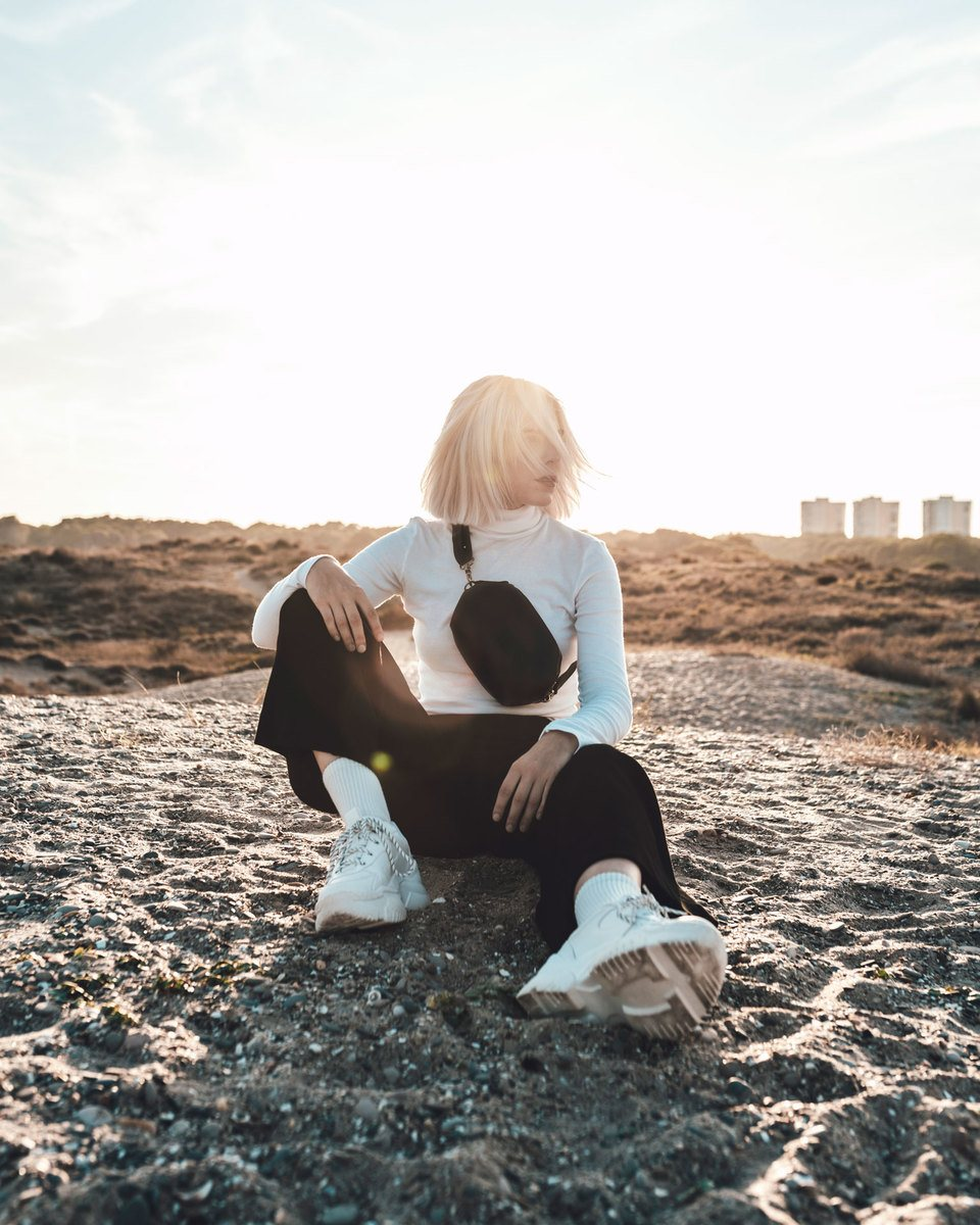Blond girl sitting on the sand with a clear sky with a white long-sleeve t-shirt and black pants wearing the Bumbag black in the crossbody mode