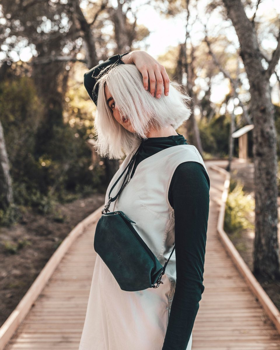 Blond girl standing in a wooden path with the hand above the head and the Bumbag green in the crossbody mode