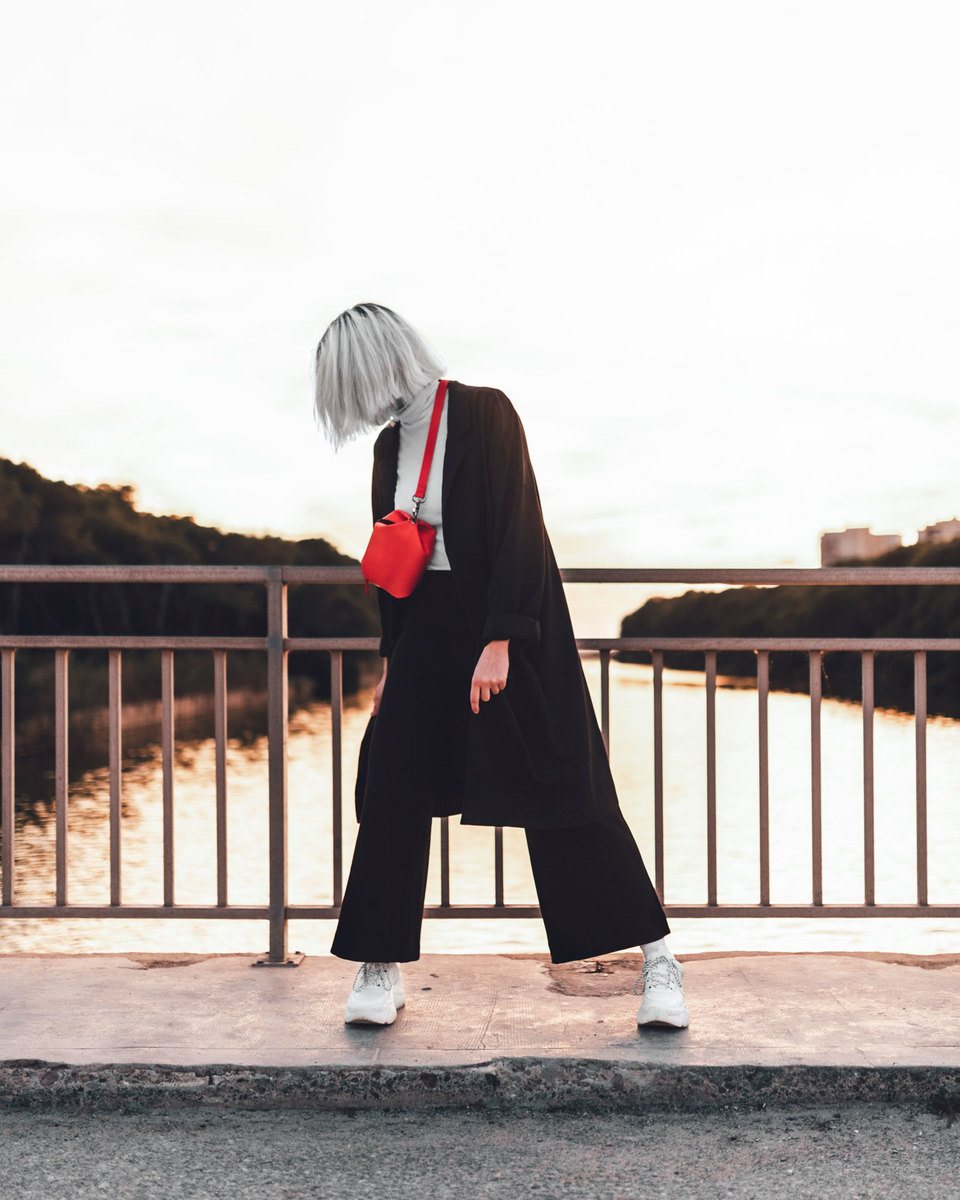 Blonde girl at sunset in a bridge over a river standing with the Bumbag red in the crossbody mode