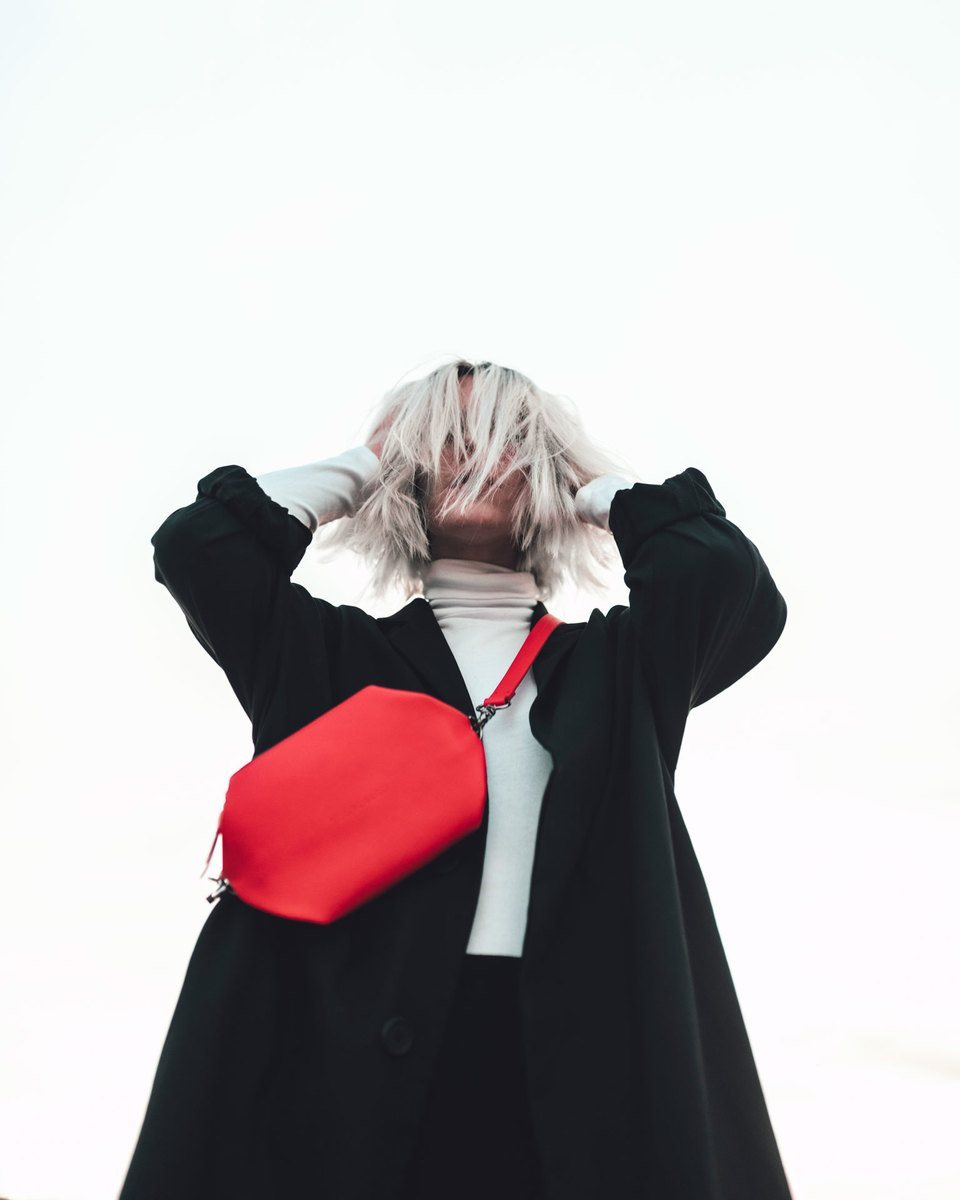 Blond girl with a black coat and her hands on the head putting the hair in her face, wearing the Bumbag red in the crossbody mode