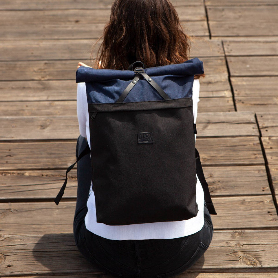 Brown haired woman from the back wearing the Folder sack blue backpack sitting on wooden steps