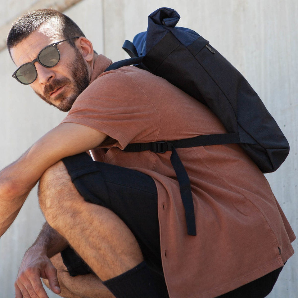 Man wearing sunglases and brown short-sleeve t-shirt with the Folder sack blue backpack