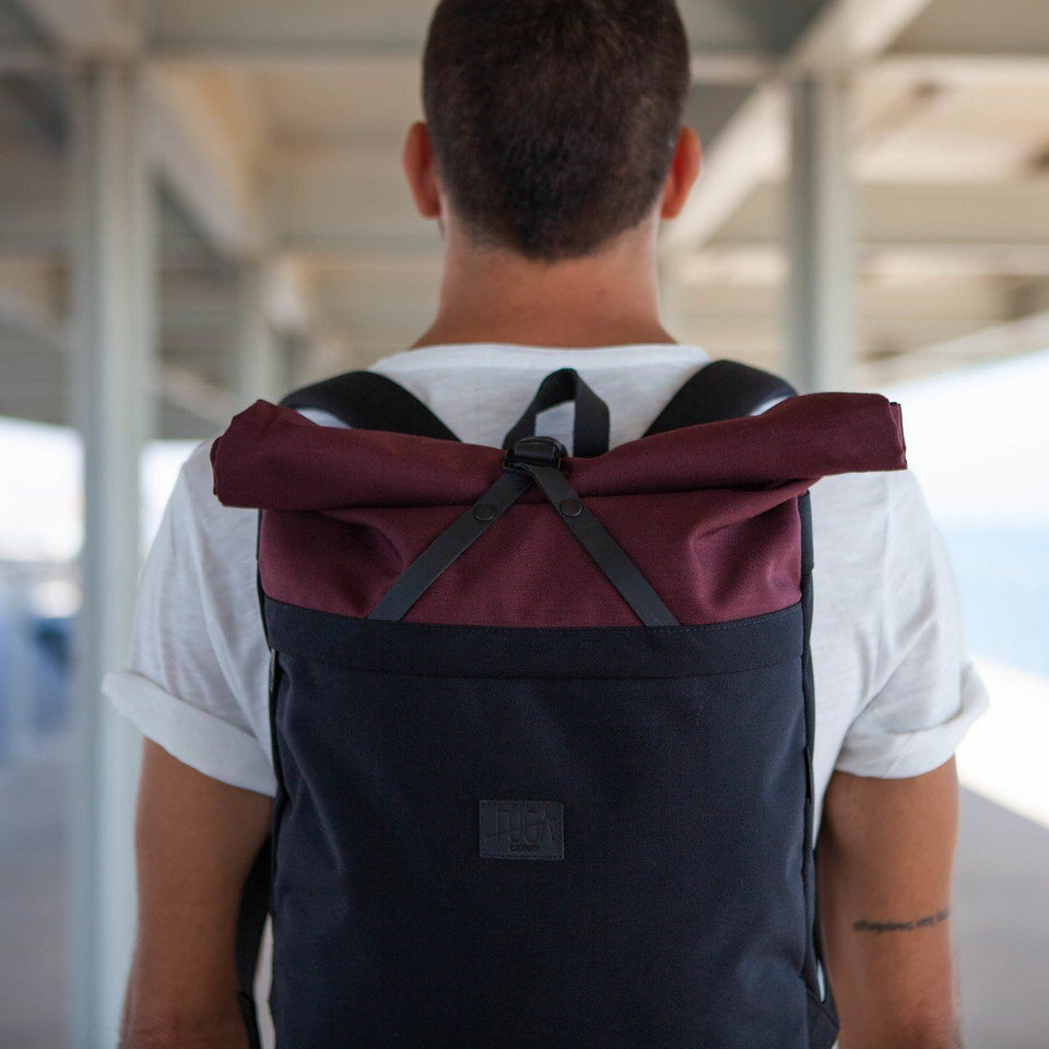 Short haired man with white short-sleeve t-shirt wearing the Folder sack bordeaux backpack from the back