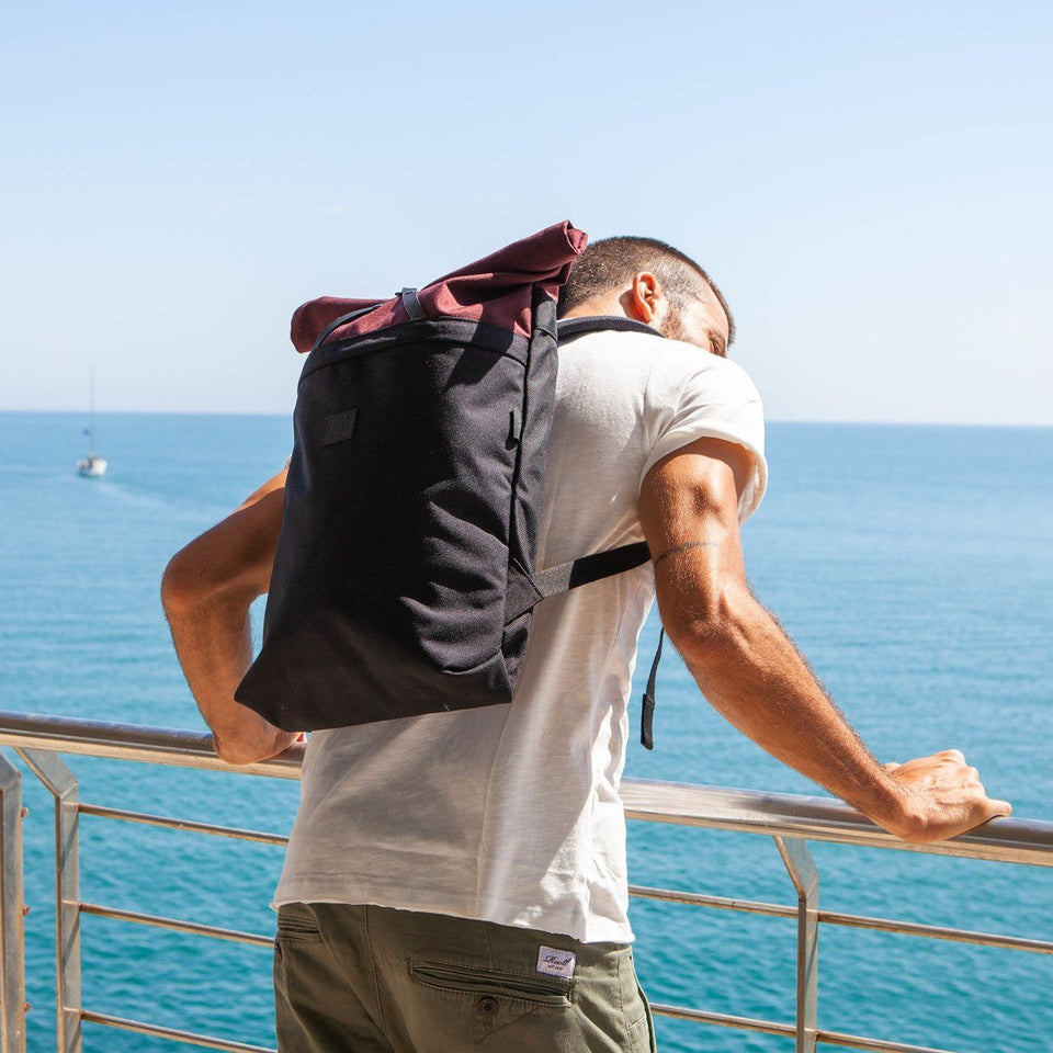 Man with white short-sleeve t-shirt wearing the Folder sack bordeax leaning on a railing with the light blue sea and clear sky as backround