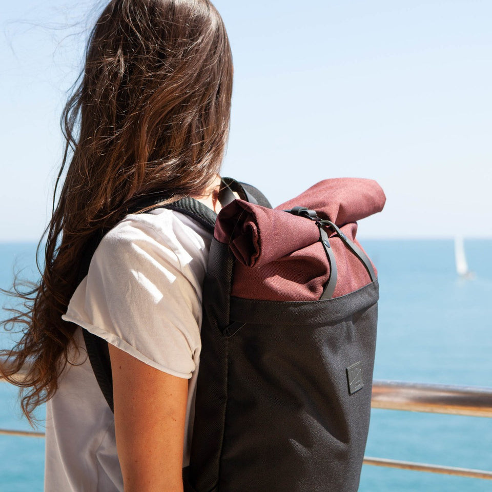 Long and dark haired girl wearing the Folder sack bordeaux with the light blue sea and clear sky as backround