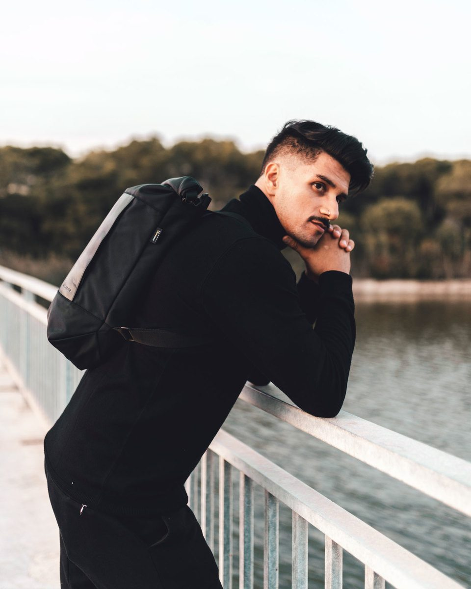Man with black hair and moustache with long-sleeve black sweater and black trousers wearing the Lean bag black in backpack mode at a bridge