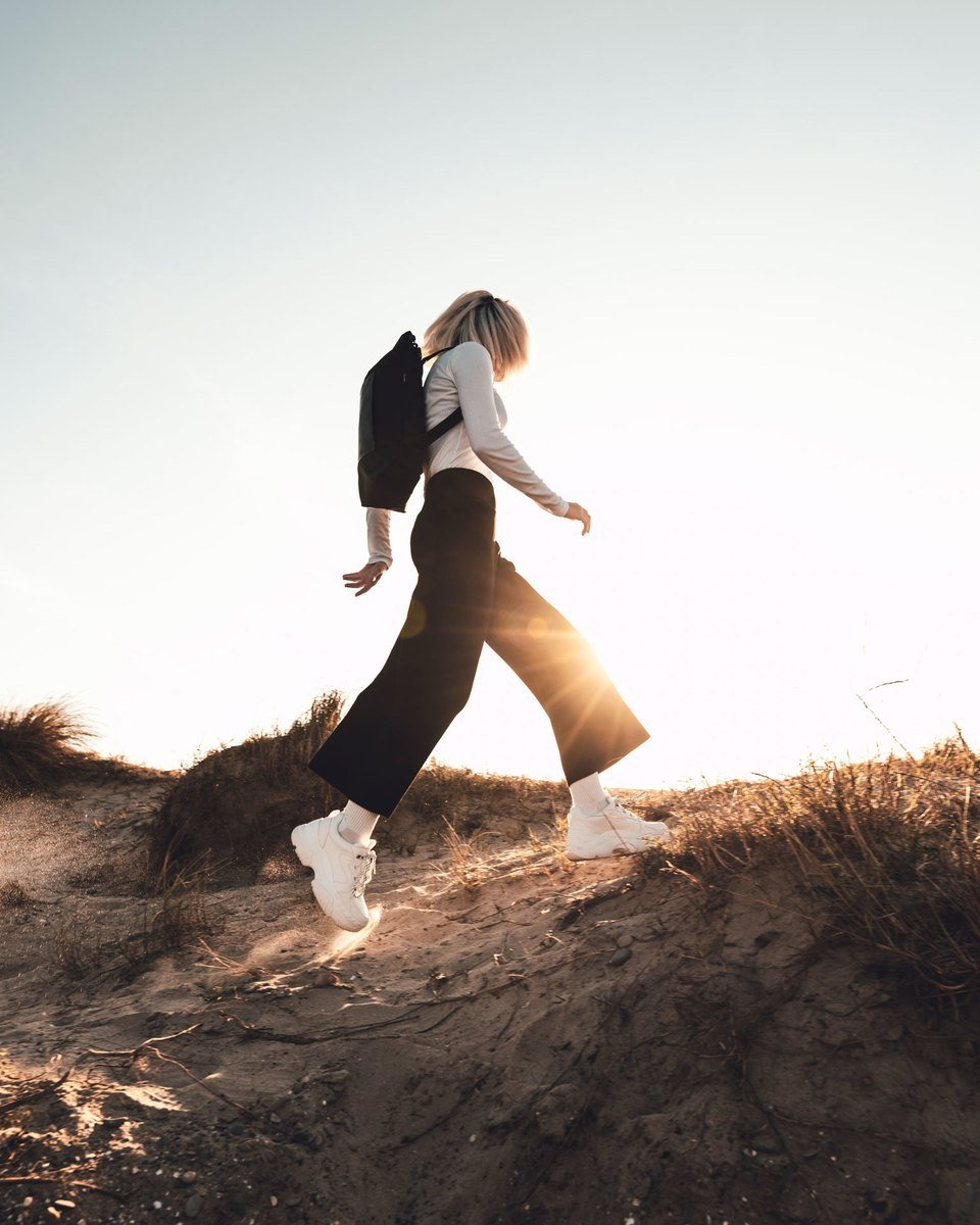 Blond girl with long-sleeve t-shirt and black pants walking through beach dunes with the Lean bag black in backpack mode
