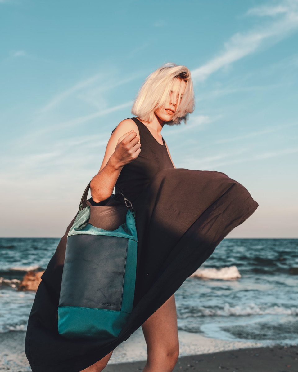 Blond girl with navy blue dress blown by the wind wearing the Lean bag blue with the sea as background and blue sky