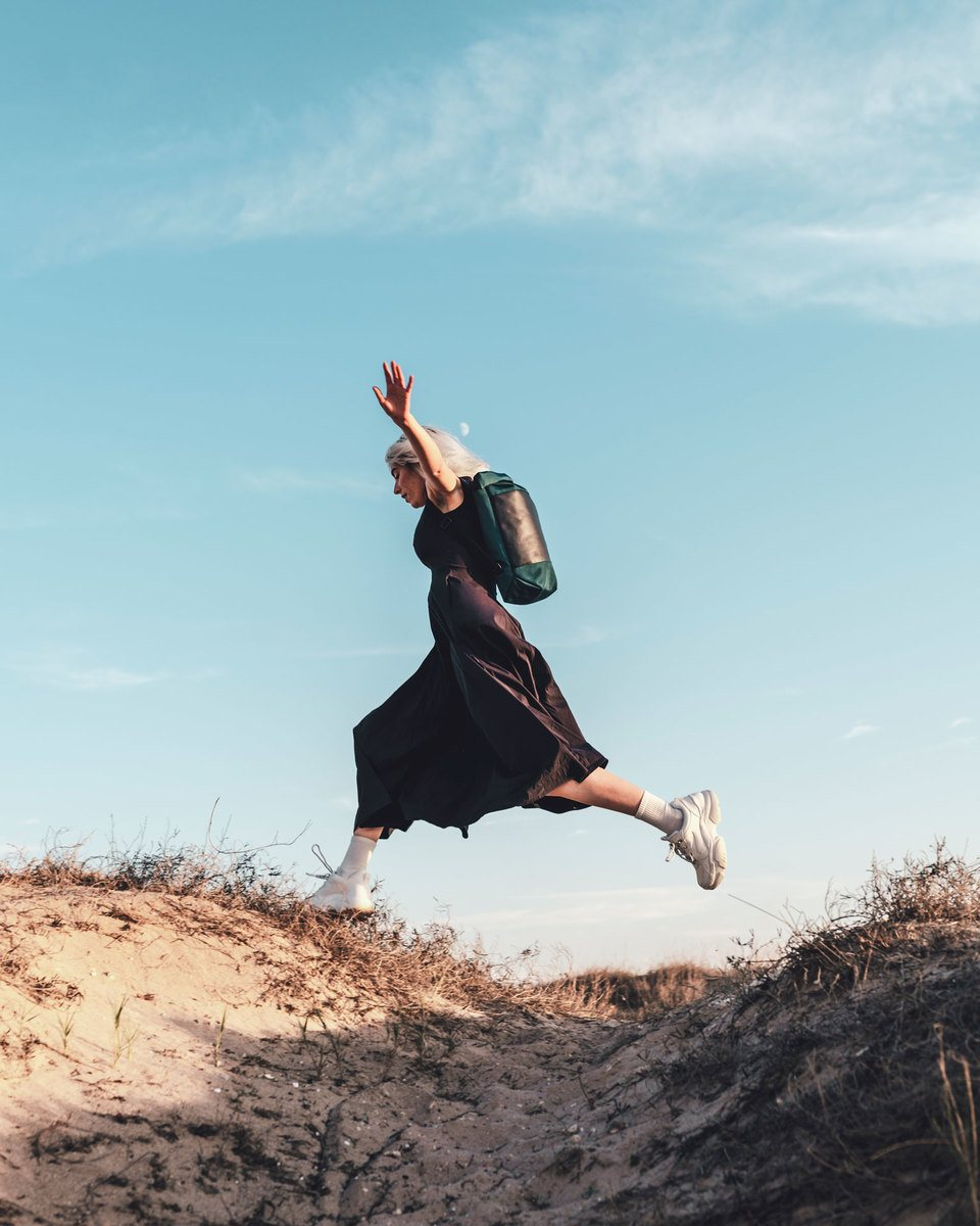 Blond girl with navy blue dress jumping in beach dune with the Lean bag blue in backpack mode