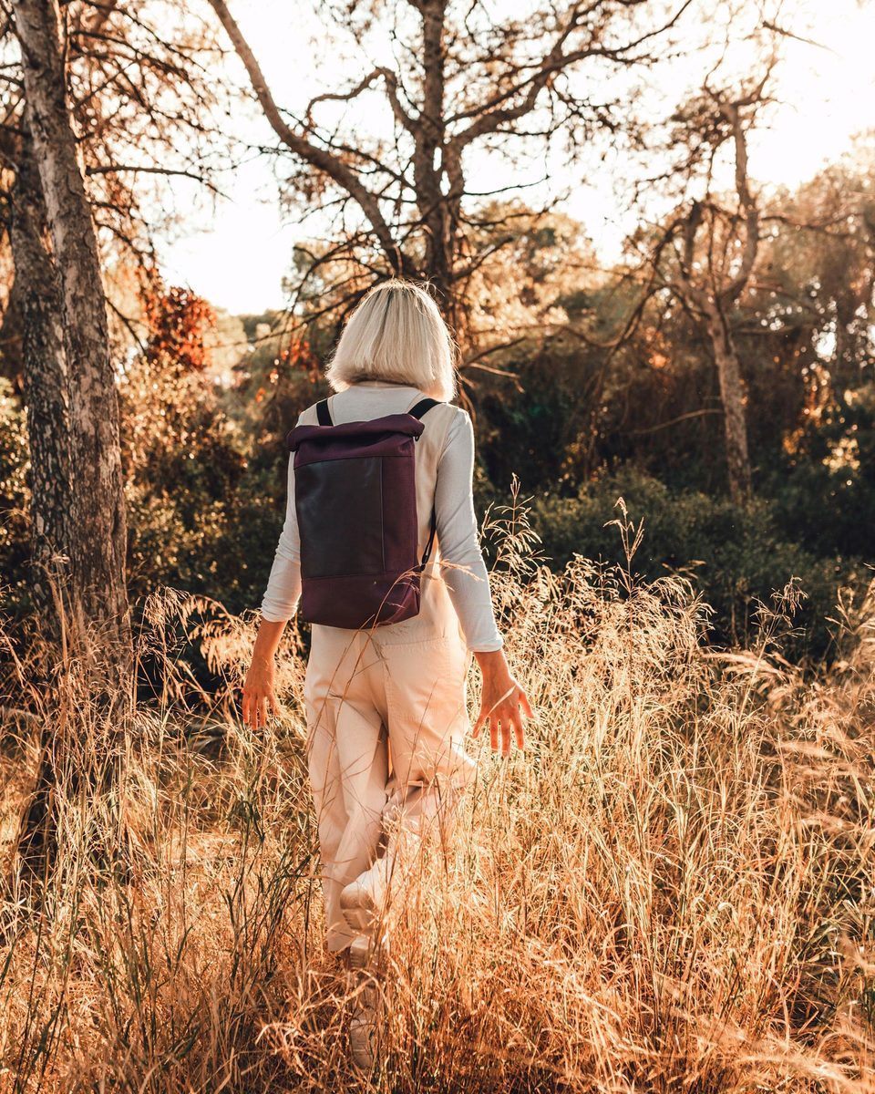 Blond girl wearing the Lean bag bordeaux walking through the forest with dramatic light