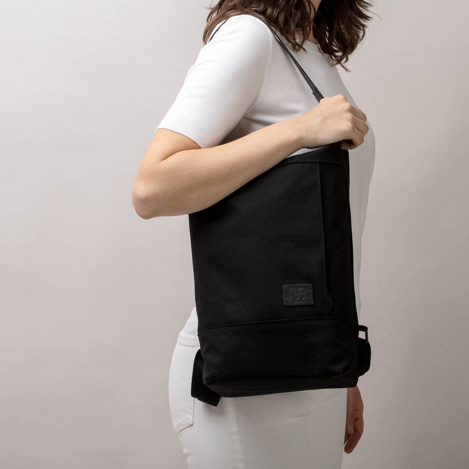 Woman with white t-shirt and trousers from the side with the Muda cotton bag black in shoulder bag mode