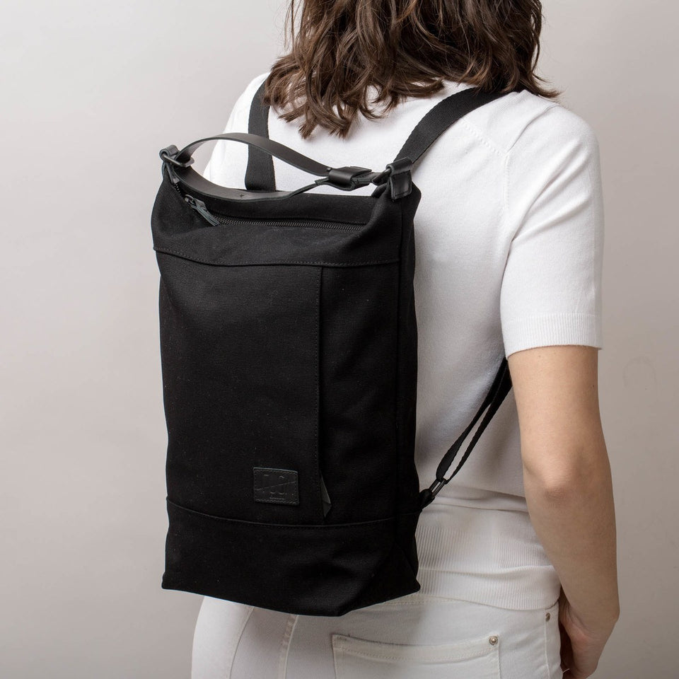Woman with white t-shirt and trousers from the back with the Muda cotton bag black in backpack mode