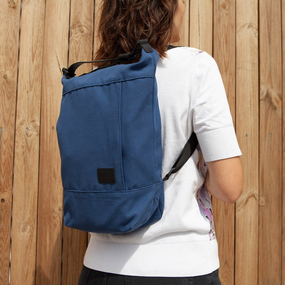 Dark haired woman from the back wearing the Muda cotton bag blue as a backpack with white t-shirt and wooden tiles wall background
