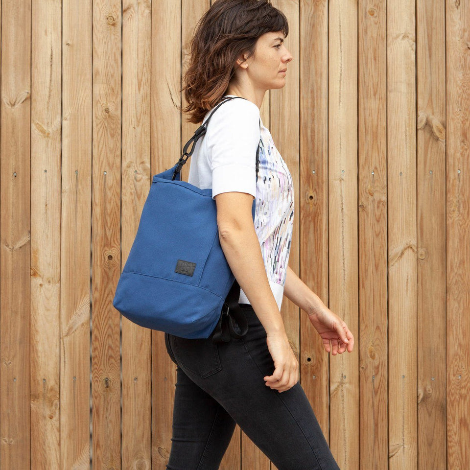 Dark haired woman from the side walking with the Muda cotton bag blue as a shoulder bag with wooden tiles wall as background