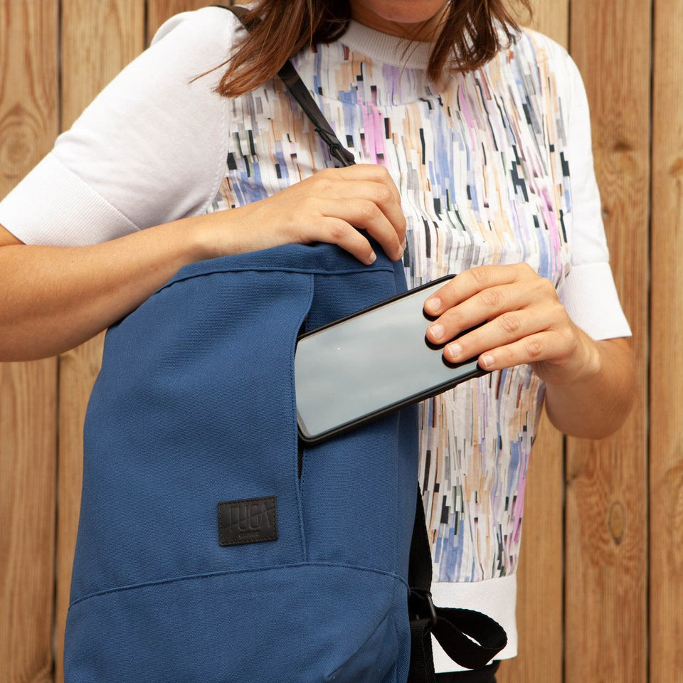 Woman with white and color printing t-shirt introducing her phone in the front zippered pocket of the Muda cotton bag blue wearing as a shoulder bag