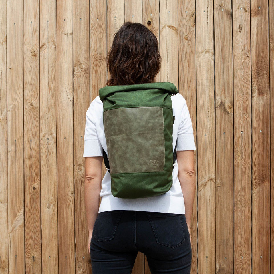 Dark haired woman with white t-shirt back view wearing the Muda leather bag green as a backpack with a wooden tiles wall background