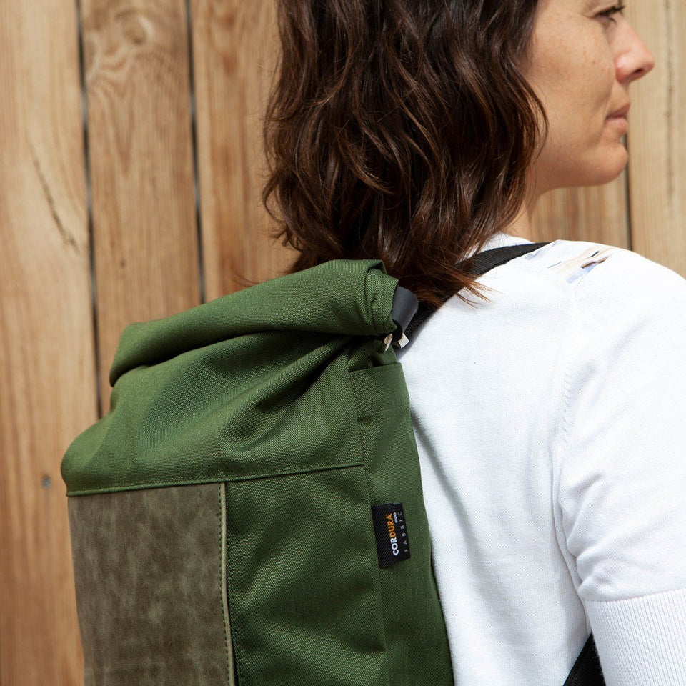 Dark haired woman with white t-shirt foreground view wearing the Muda leather bag green as a backpack with a wooden tiles wall background