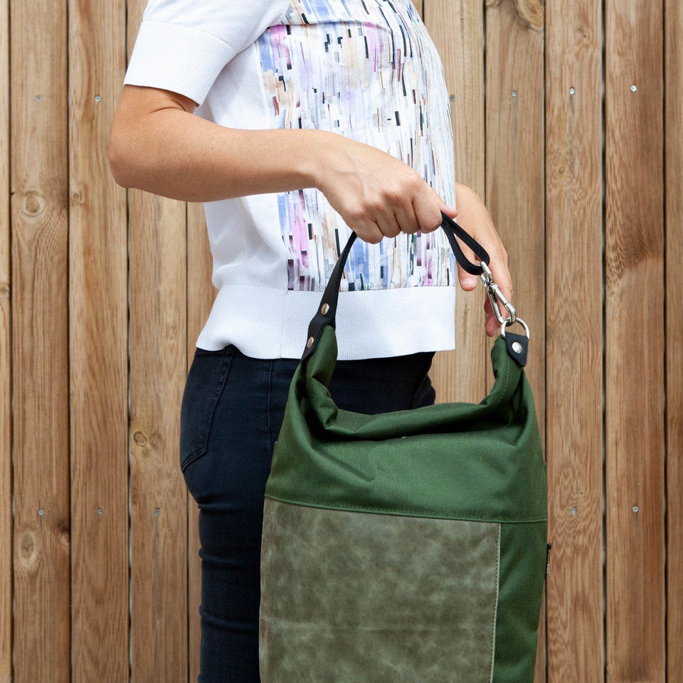 Woman with white t-shirt side view wearing the Muda leather bag green as a hand bag with a wooden tiles wall background