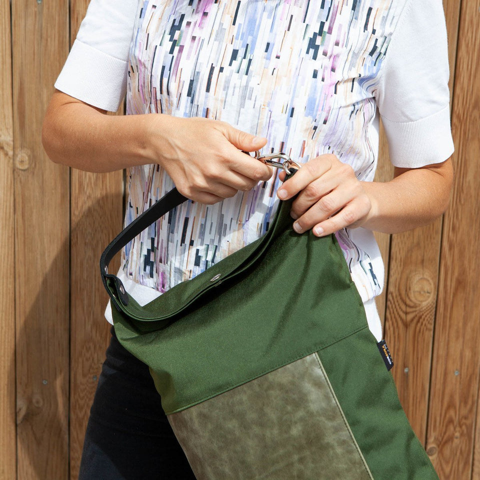 Woman with white t-shirt foreground view opening the Muda leather bag green with a wooden tiles wall background