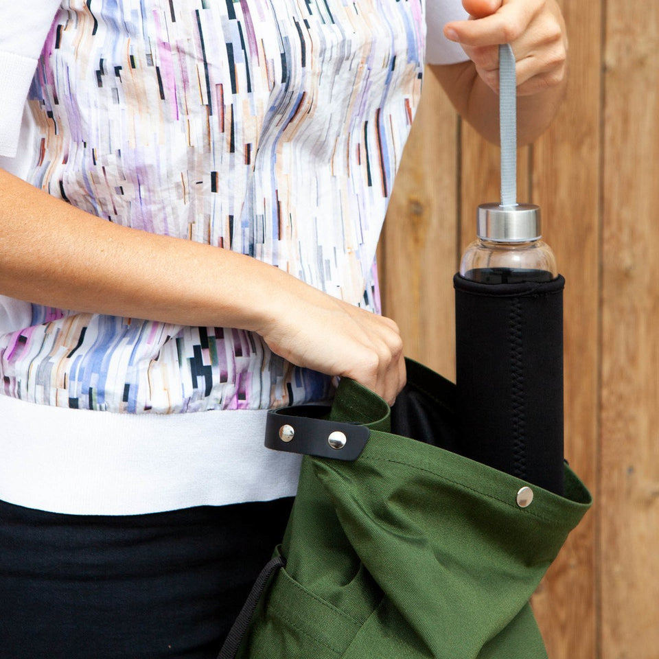 Woman with white t-shirt detail view introducing a water bottle in the the Muda leather bag green with a wooden tiles wall background